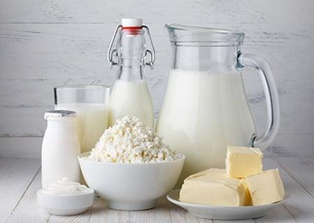Mesa com jarra e garrafas de leite, manteiga e queijos