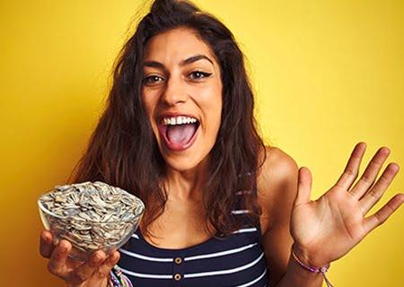 Mulher segurando tigela de sementes (alimentos que aumentam a serotonina) e sorrindo