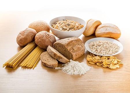 Mesa com alimentos crus: cereais, macarrão, farinhas e pães