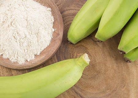 Banana verde ao lado de pote de farinha