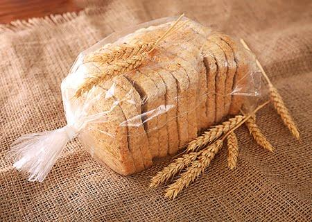 Pão de fôrma fatiado sobre mesa, em embalagem de plástico sobre saco de juta e ramos de trigo ao lado