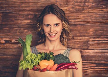 Mulher sorrindo segurando cesta de vegetais