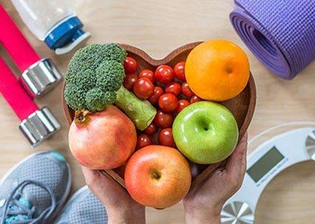 Mão segurando tigela em forma de coração com maçãs, laranja, brócolis e tomates-cereja