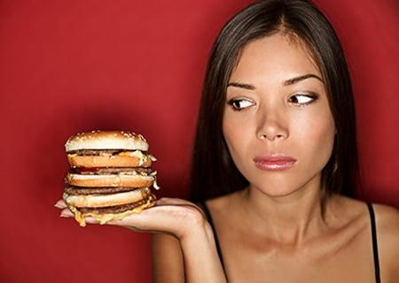 Mulher olhando para sanduíche com expressão de dúvida, se come ou não