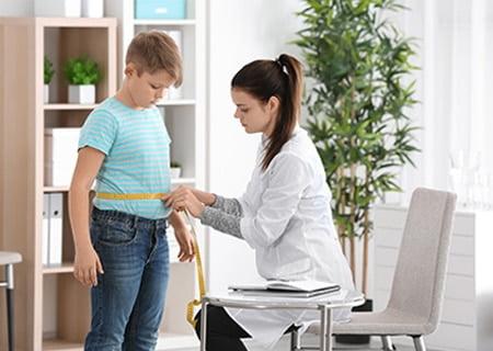 Médica medindo cintura de menino com fita métrica