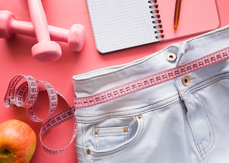Shorts jeans com fita métrica por cima, caderno e halteres