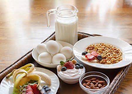 Bandeja de um café da manhã saudável: com jarra de leite, pote com ovos, prato com iogurte e frutas...