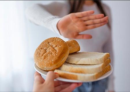 Uma pessoa oferecendo pães e outra negando. Muita gente acha que cortar glúten da dieta ajuda a emagrecer.