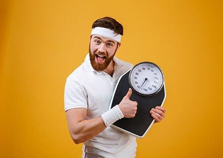Homem com roupa de ginástica segurando balança
