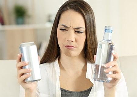 Mulher segurando uma bebida dietética em uma mão e, na outra, uma garrafa de água, com expressão de dúvida sobre o que tomar