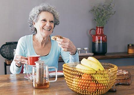 Mulher idosa sentada sorrindo tomando café da manhã em mesa com café e cesta de frutas