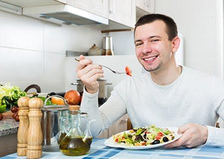 Homem sorrindo sentado à mesa comendo prato cheio de legumes, que faz parte de uma alimentação adequada para prevenir e tratar o câncer de próstata.
