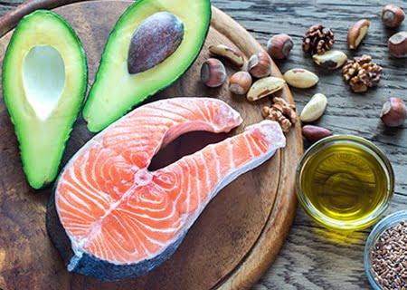 Mesa com abacate, salmão, azeite e castanhas, alguns alimentos que ajudam a regular a tireoide