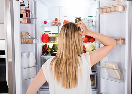 Mulher de costas, olhando para uma geladeira aberta, com a mão na cabeça, pensativa.