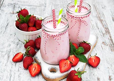 Iogurte de morango dentro de copos de vidro em cima da mesa, com morangos fatiados ao redor. Opções de bebidas saudáveis para crianças