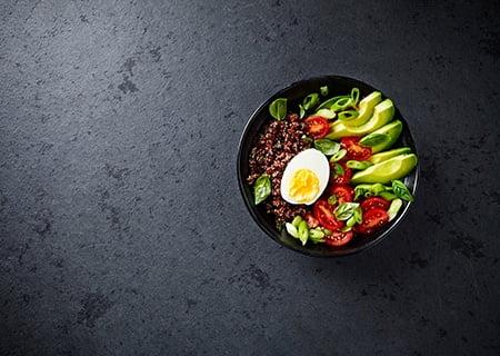 Tigela do buda sobre mesa. Ela contém alimentos como abacate, ovo cozido e tomate
