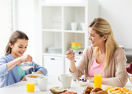 Mãe e filha sentadas à mesa tomando café da manhã e sorrindo, Na mesa tem sucos, leite e pães