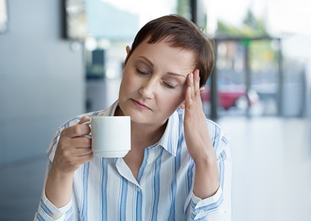 Mulher sentada segura uma xícara de café em uma mão, enquanto apoia a outra mão sobre a testa. De olhos fechados, ela passa a impressão de cansaço e sensação de dor de cabeça