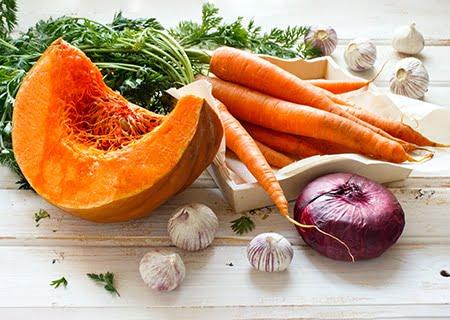 Mesa com cenouras, melão, alho e cebolas - exemplos de alimentos antioxidantes que atuam na prevenção do câncer de pele