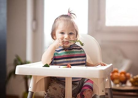 Garotinha sentada em caldeirão comendo um legume com as mãos, praticando a alimentação BLW