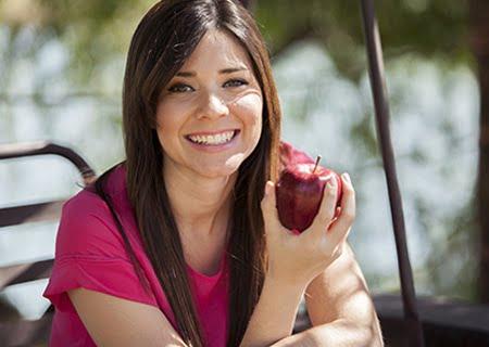 Moça sorrindo segurando maçã na mão