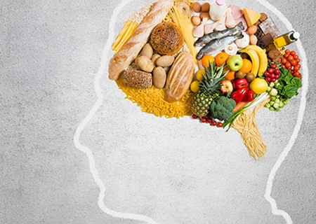 Desenho de cabeça com alimentos no lugar do cérebro, entre frutas, legumes e vegetais