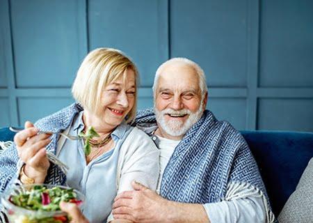 Uma mulher idosa e um homem idosos sorrindo. Ela olha para ele e ele, para a câmera