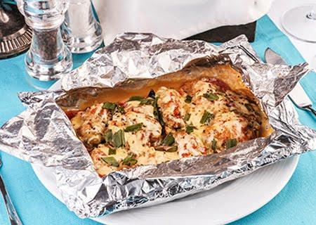 Peixe dentro de papel-alumínio servido em prato