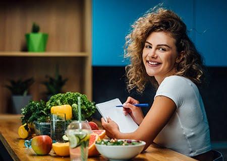 Mulher sentada ao lado de mesa repleta de alimentos saudáveis, como frutas e verduras, fazendo anotações em um caderno e sorrindo