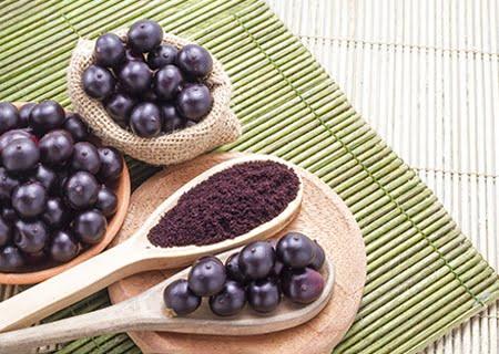Mesa com colheres de pau e diversos tipos de açaí, em fruta, em pó... A fruta pode ser uma aliada de quem está com sobrepeso.