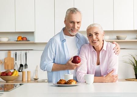Casal de idosos sorrindo, apoiados em banqueta. O senhor abraça a senhora e, com a outra mão, segura uma maçã