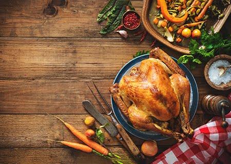 Mesa com peru assado, cenouras, vegetais e facas