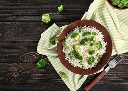 Tigela marrom sobre toalha listrada de verde e branco. Dentro do recipiente está arroz com brócolis, além de pedaços de brócolis em cima da mesa, que serve de apoio para os itens