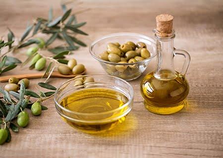 Mesa com azeite em garrafa e pote de vidro e outro pote com azeitonas, além de folhas de oliveira espalhadas