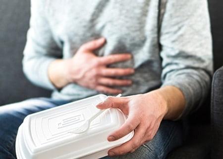 Homem segura com uma mão uma embalagem de marmita de isopor e um garfo de plástico e, com a outra, coloca a mão sobre a barriga, indicando desconforto.