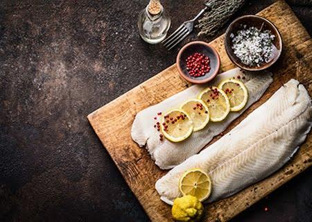 Sobre mesa, tábua de madeira com peixe, rodelas de limão e especiarias