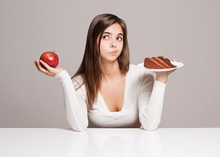 Mulher com cara de dúvida segurando em uma mão uma maçã e na outra um prato com uma fatia de bolo. Ela tem cabelos compridos lisos e usa uma blusa de mangas compridas branca.