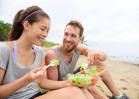 Uma mulher e um homem sentados na praia, com roupas de ginástica, sorrindo e comendo salada