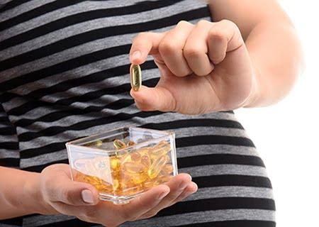 Mulher grávida segurando pílulas de ômega 3