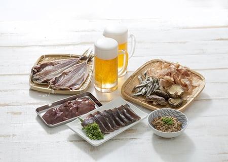 Mesa com carnes e copos de cerveja, alguns dos alimentos ricos em purinas
