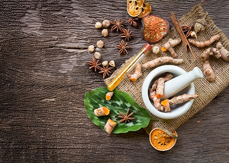 Mesa com alguns alimentos da dieta indiana, como cúrcuma e gengibre