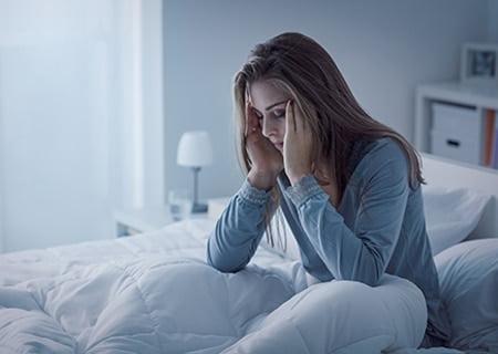 Mulher na cama sentada com os olhos fechados e as mãos na cabeça, indicando desconforto provocado pela insônia