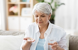 Senhora segura um comprimido em uma mão e, na outra, um copo d'água.