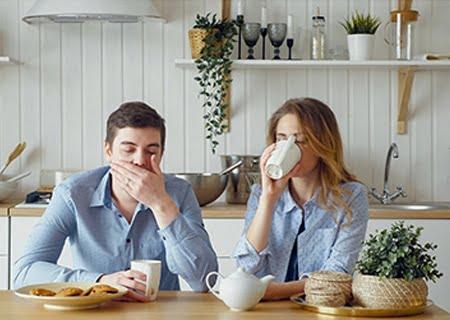 Homem e mulher sentados à mesa com expressão de cansaço tomando em caneca