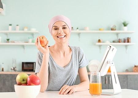 Mulher sentada à mesa sorrindo e segurando uma maçã. Ela veste lenço na cabeça.