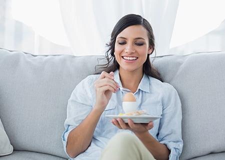 Mulher sentada sorrindo segurando um ovo em um porta-ovos e uma colher.