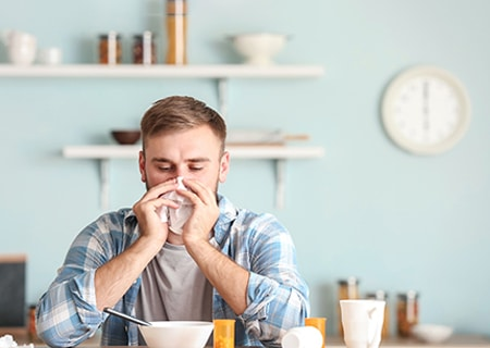 Homem sentado à mesa soa o nariz com um lenço de papel. Na semana tem uma tigela de comida, uma caneca e medicamentos.