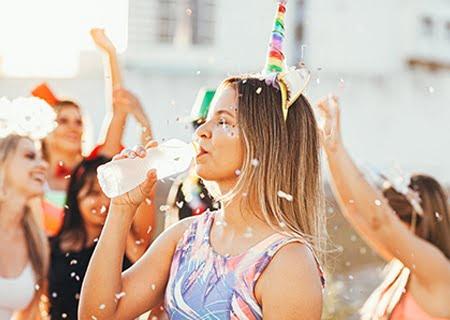 Menina no meio de festa de Carnaval, com uma tiara de unicórnio, bebendo água em garrafa