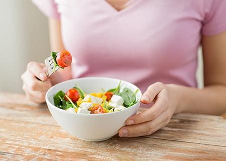 Mulher comendo salada. Ela veste uma camisa rosa e segura um tomate-cereja no garfo.