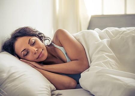 Mulher dormindo. Ela está deitada de lado, com as mãos embaixo do rosto, e esboça um sorriso. Um edredom branco a cobre até o tronco.